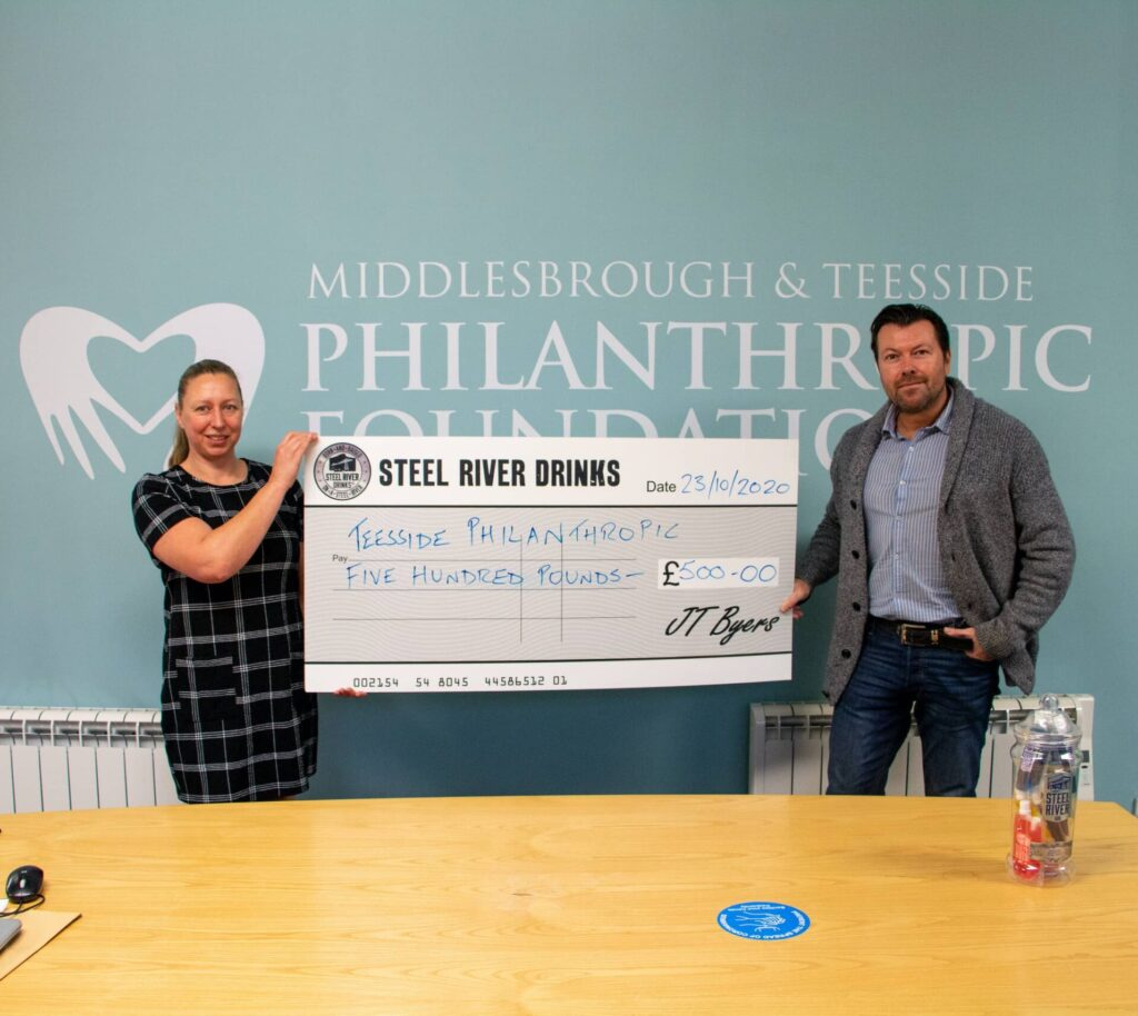 Jay holding oversized £500 cheque with Trustee from Middlesbrough and Teesside Philanthropic Foundation