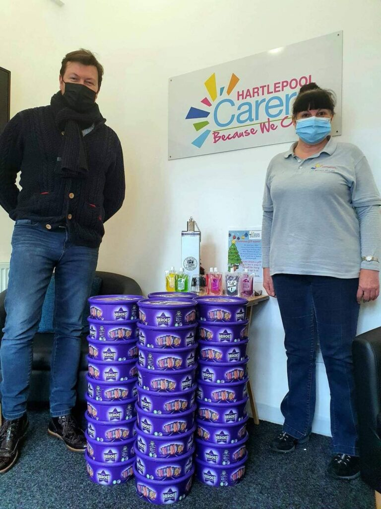 Jay stood with Hartlepool Carers employee next to large pile of stacked Cadbury's Heroes Boxes