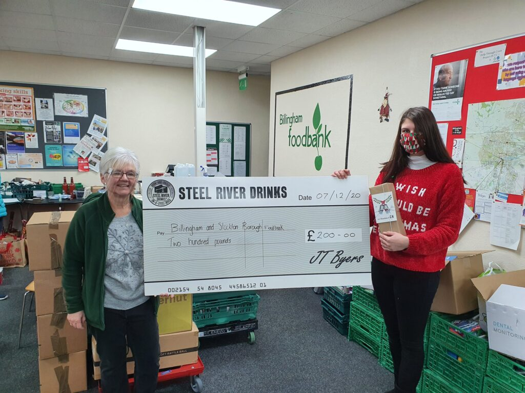 Large Steel River Cheque held up by Steel River Employee and Volunteer at Billingham Foodbank