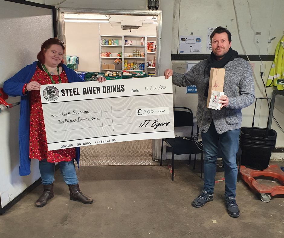 Large Steel River Cheque held up by Jay Byers and Volunteer at NQA Foodbank