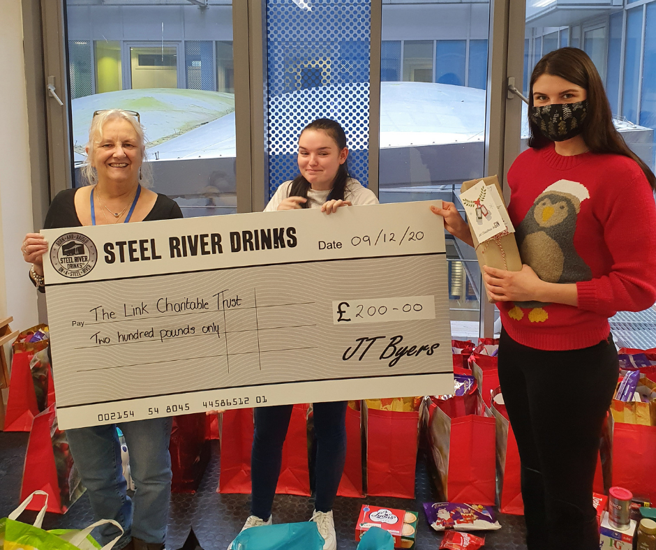 Large Steel River Cheque held up by Steel River Employee and Volunteers from the Link Charitable Trust