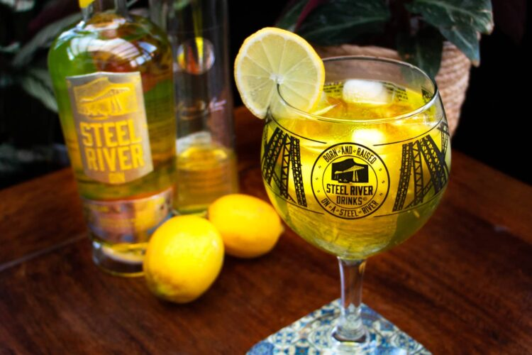 Steel River Goblet with Club Tropicana Gin and Lemoncello cocktail. Slice of lemon on glass to Garnish.
