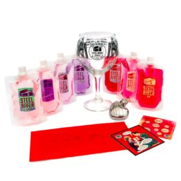 Steel River Valentines Gin Gift with Seven different mini pouches in, all filled with gin ranging in hues from purple to scarlet. Steel River Goblet and heart shaed ginflask in centre, with two valentines coasters and red envelope containing Valentines letter.