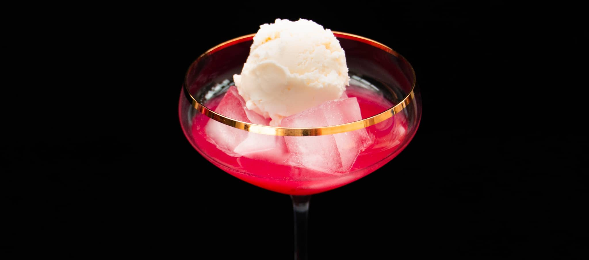 Pink Raspberry Ripple Gin Cocktail with vanilla ice-cream as garnish in centre.