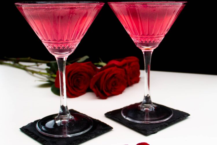 Two martini Glasses filled with a pink gin and prosecco cocktail. Strawberry garnish in the shape of a heart and roses in the background.