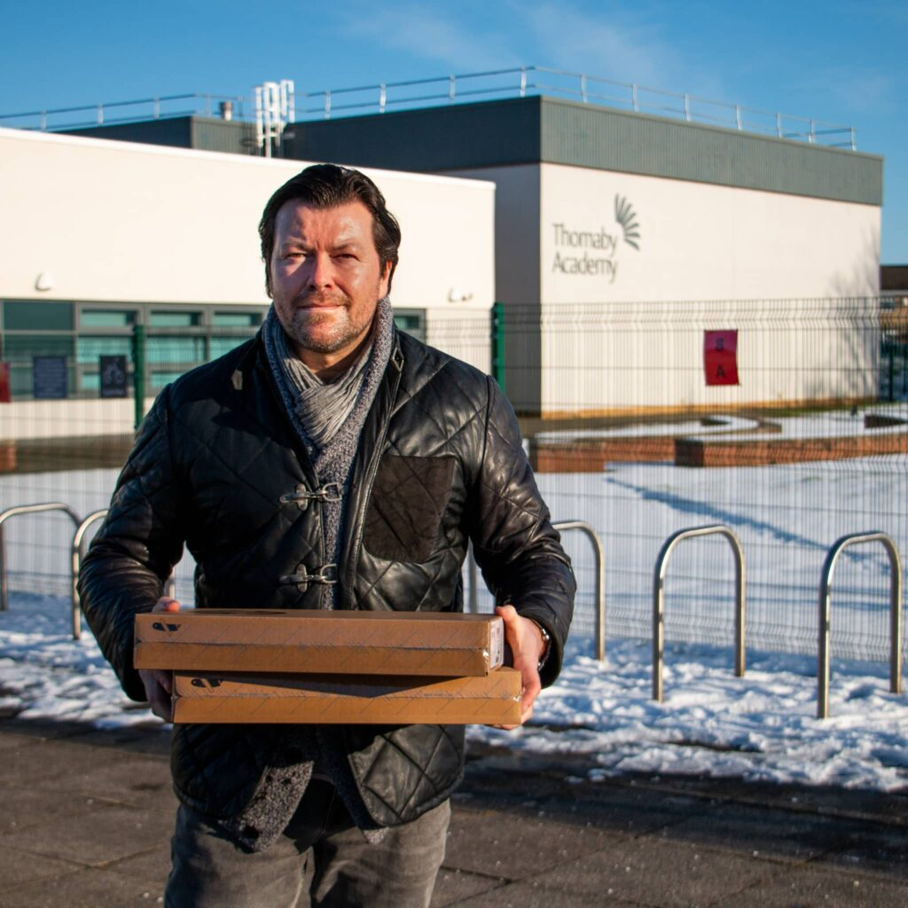 Jay holding HP chromebooks in front of Thornaby Academy