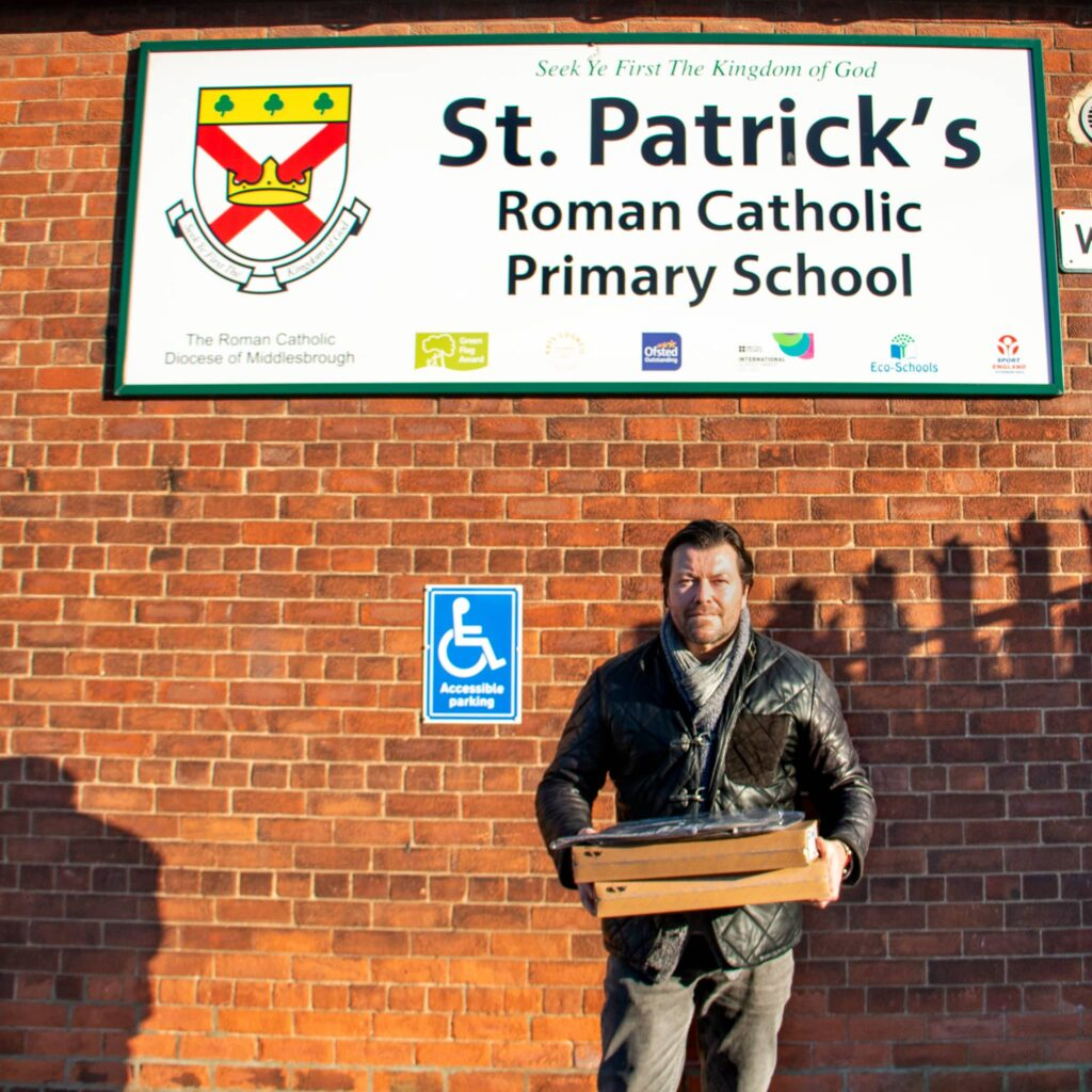 Jay holding Chromebooks in front of St Patricks primary school