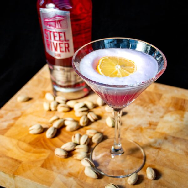 Martini Glass with Pink Sours in, white foam top and slice of lemon to garnish. Bottle of El Clasico Gin in the background, with pistatchio nuts strewn across the table.