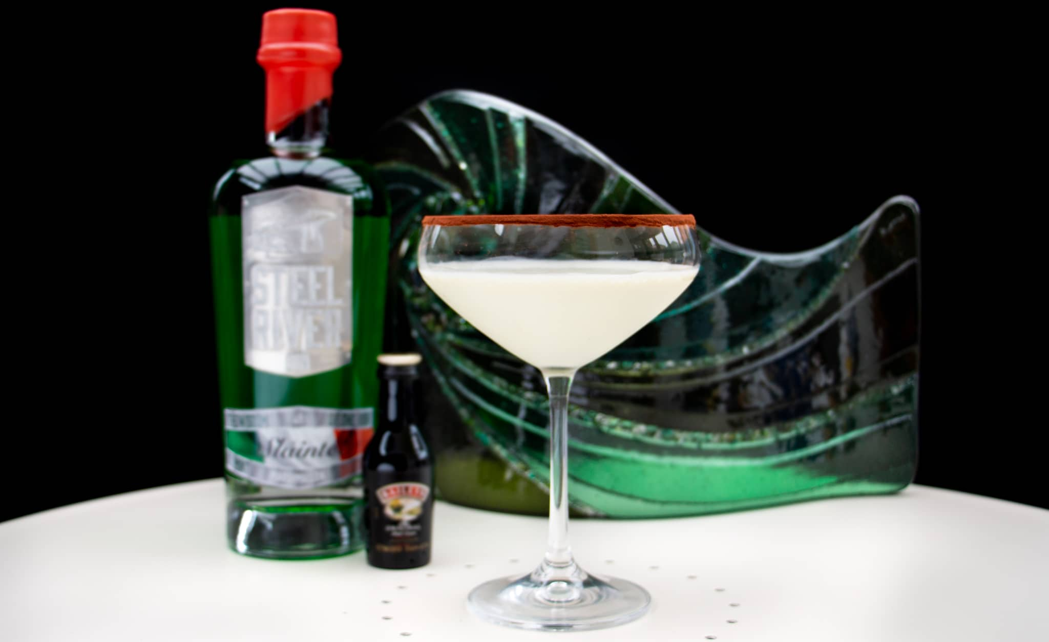Irish Cream Martini in a glass rimmed with chocolate. Small baileys bottle and 70cl Green gin bottle